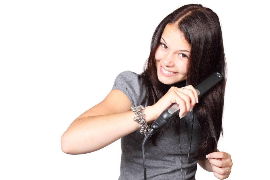 Kvinde glatter hår med glattejern